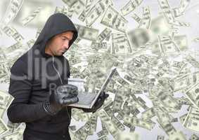 Criminal in hood on laptop in front of lots of money