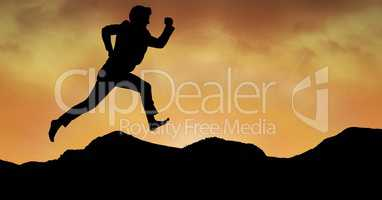 Silhouette business person running over mountains against orange sky