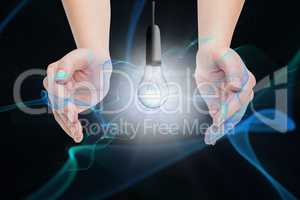 Digital composite image of hand covering electric bulb against black background