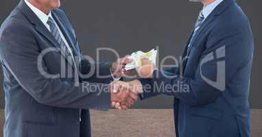 Midsection of businessmen holding money representing corruption concept