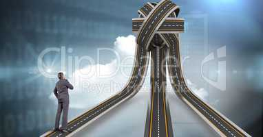 Digital composite image of businessman standing on jumbled highway
