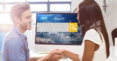 Smiling man and woman shaking hands with search screen on monitor
