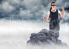 Business woman blindfolded on misty mountain peak against storm clouds
