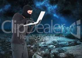 Criminal Man in balaclava on laptop in front of landscape at night