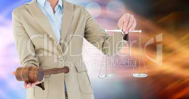 Midsection of judge holding gavel and law scales