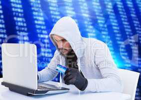 Criminal in hood on laptop with card in front of numbers
