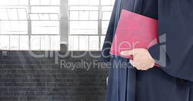 Judge holding book in front of windows and brick wall