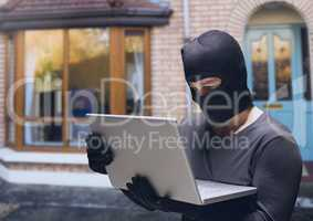 Criminal in hood on laptop in front of home house