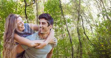 Happy man giving piggy back ride to woman in forest