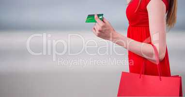 Midsection of woman with purse holding credit card against blurred background