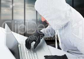 Criminal in hood with laptop in front of window