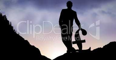 Silhouette of businessman with pound sign on mountain