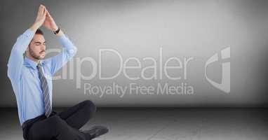 Business man meditating with hand over head in grey room