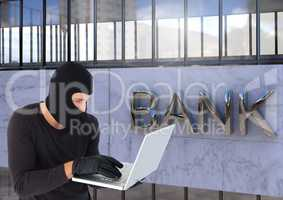 Criminal in hood on laptop in front of bank