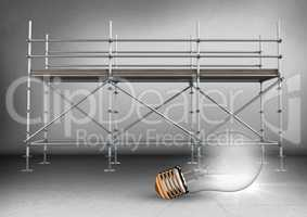 Lightbulb in front of scaffolding in grey room