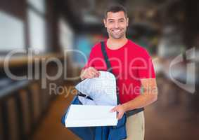 Happy deliveryman with delivery bag and pizza boxes in the city at night