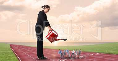 Businesswoman watering employees on running tracks against cloudy sky