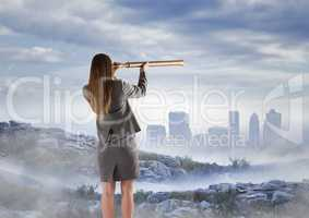 Business woman observing skyline with telescope from misty mountain peak