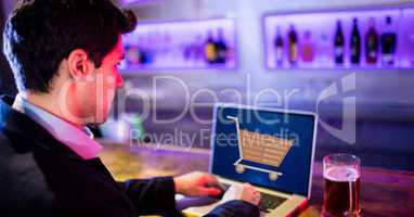 Businessman using laptop with shopping cart on screen