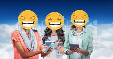 Digitally generated image of female  friends faces covered with emoji using digital tablet against s