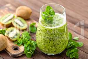 Fresh green kiwi smoothie with mint and honey, healthy organic drink on wooden table
