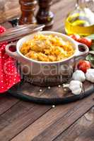 Stewed cabbage with meat on dark rustic wooden background