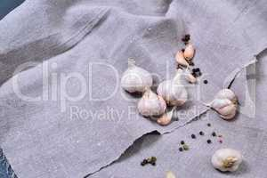 Garlic in husk on gray fabric, top view