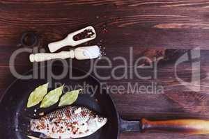 River fish carp with spices in a black cast-iron frying pan