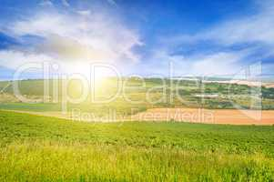 hilly terrain, spring field and sunrise on blue sky