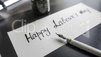Happy labour's day calligraphy and lattering post card. Left view with calligraph pen.