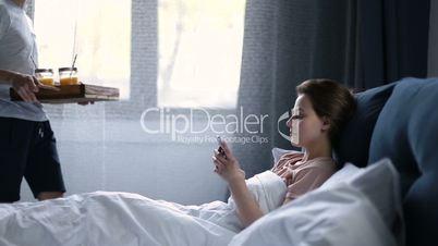 Smiling couple having breakfast in bed in morning