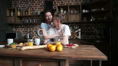 Happy couple in love embracing in the kitchen