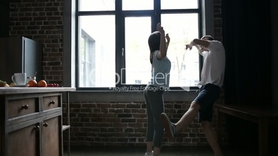 Dancing couple having fun in modern kitchen
