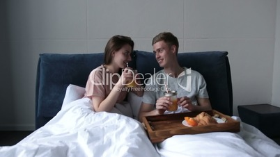 Young couple sharing breakfast in bed at home