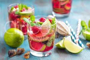 Refreshing mint cocktail mojito with rum, lime and raspberry, cold drink or beverage