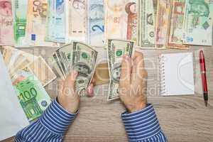 Banker counting Dollars at his office table, Empty Notebook World currencies around him