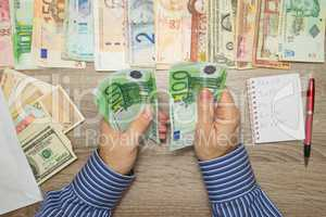 Banker counting Euro at his office table, Empty Notebook World currencies around him