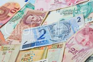 Background from paper money of the different countries. Brazilian real in the middle