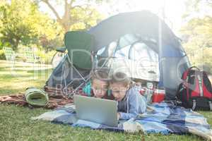 Siblings using laptop outside the tent