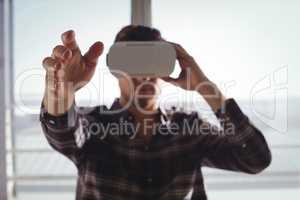 Businessman gesturing while using virtual reality headset in office