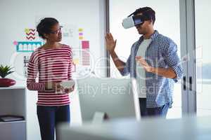 Female colleague assisting businessman while using virtual reality headset