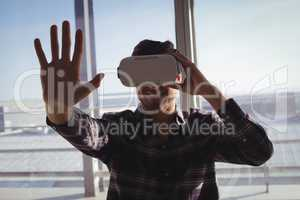 Businessman experiencing virtual reality in creative office
