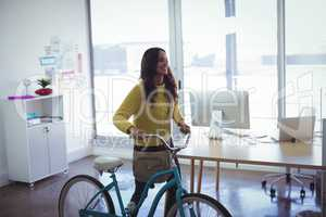 Businesswoman with bicycle in office