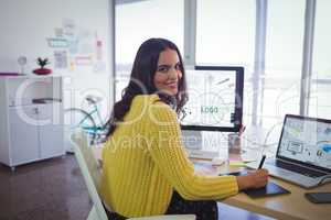 Smiling female graphic designer working in creative office