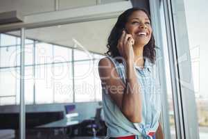Smiling businesswoman talking on phone by window