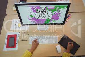 Hands of female designer using digitizer and computer in creative office