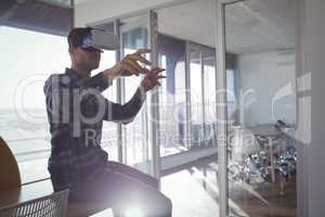 Businessman gesturing while experiencing virtual reality in office