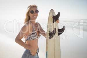 Portrait of happy woman holding surfboard at beach