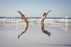 Side view of happy couple jumping on shore at