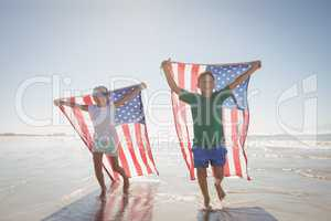 Siblings holding American flags while running at beach